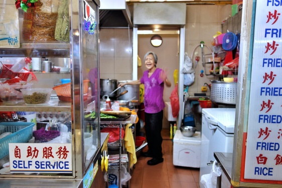 Hawker selling hor fun, fish porridge, and other Singaporean food at a hawker centre at Holland Village | ShopkeeperStories.com
