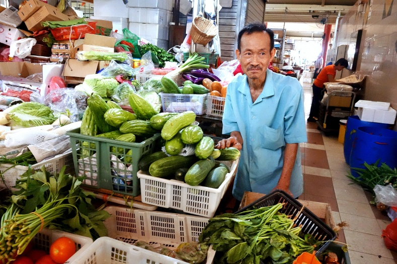 Market vendor selling vegetables in Singapore: bitter gourd, tomatoes, bok choy