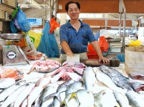 Fishmonger in the Jurong East market in Singapore selling golden pomfret fish - Shopkeeper Stories