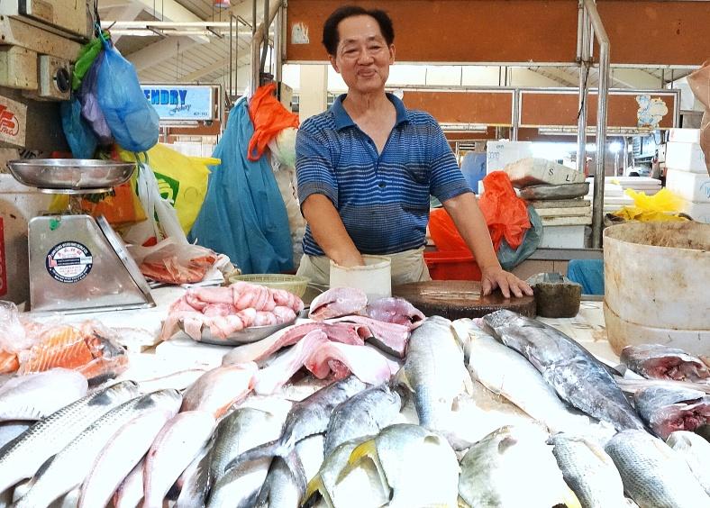 Fishmonger in the Jurong East market in Singapore selling golden pomfret fish - Shopkeeper Stories