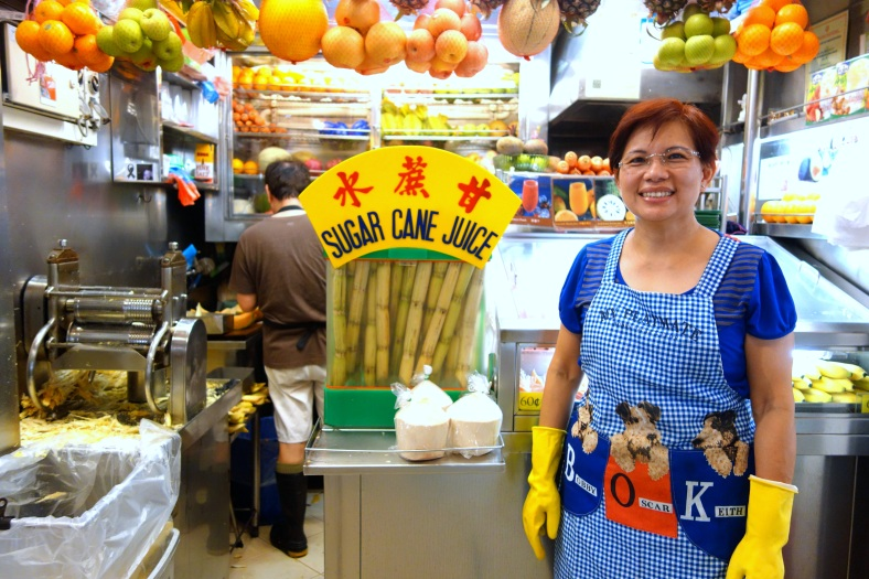 Hawker in Singapore selling fresh fruit juices including sugar cane, star fruit, coconuts, and more | Shopkeeper Stories