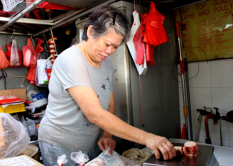 Butcher of frozen meat at a wet market in Toa Payoh, Singapore | Shopkeeper Stories
