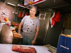 Butcher at a market in Toa Payoh, Singapore selling frozen meat such as beef and lamb | ShopkeeperStories.com